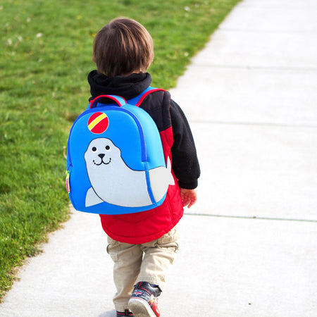 Preschooler  wearing a blue backpack with grey sea lion design on the front of the bag.  Sea Lion is looking up at a ball.  Tail wraps around to side panel.