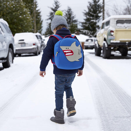 Young boy stomping through snow wearing shark-theme backpack.