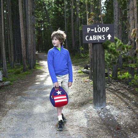 Young male hiker  carries the patriotic red and white and blue washable lunch-bag.   Lunchbag is made from a sustainable lightweight material.