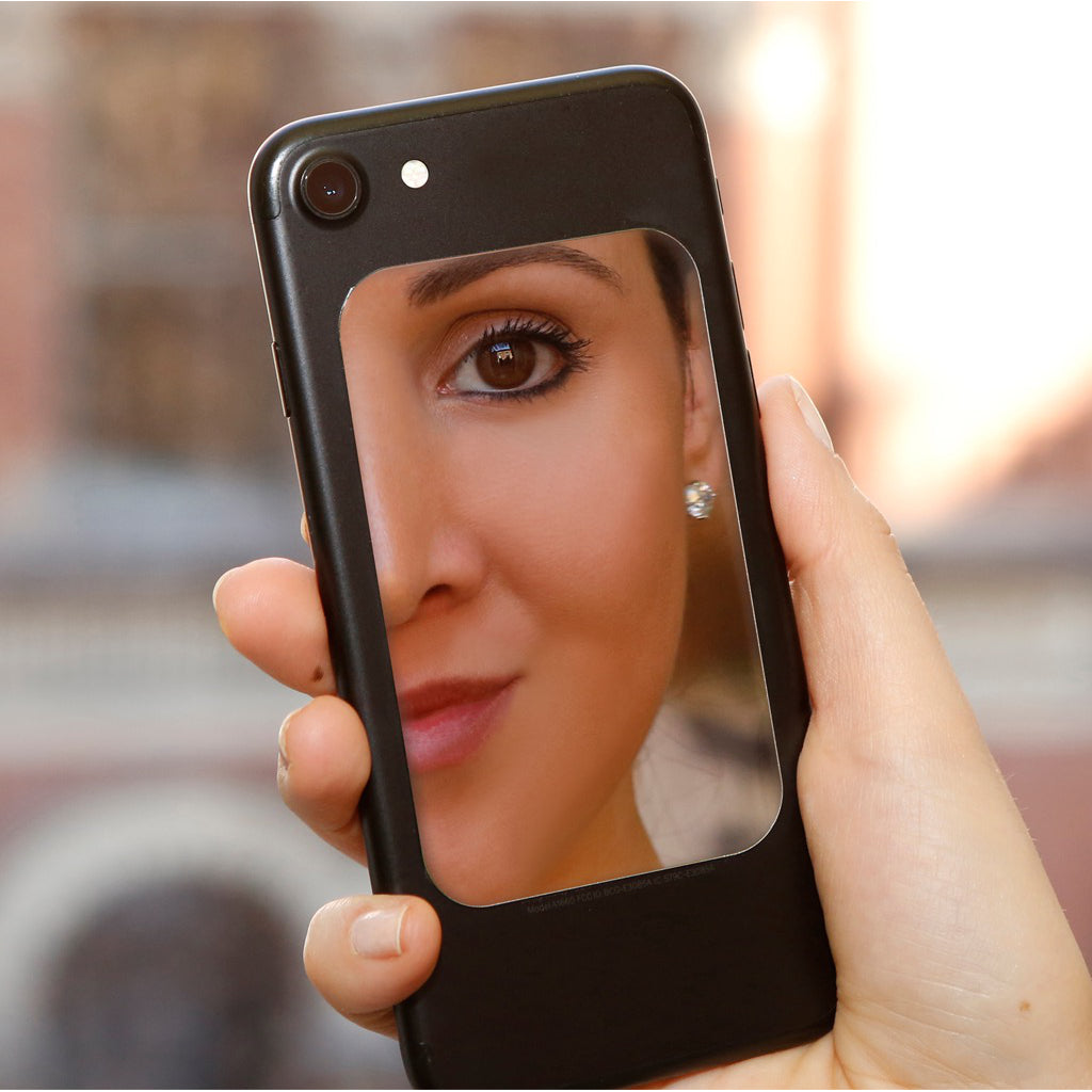 Closeup of woman looking in Phone Mirror.