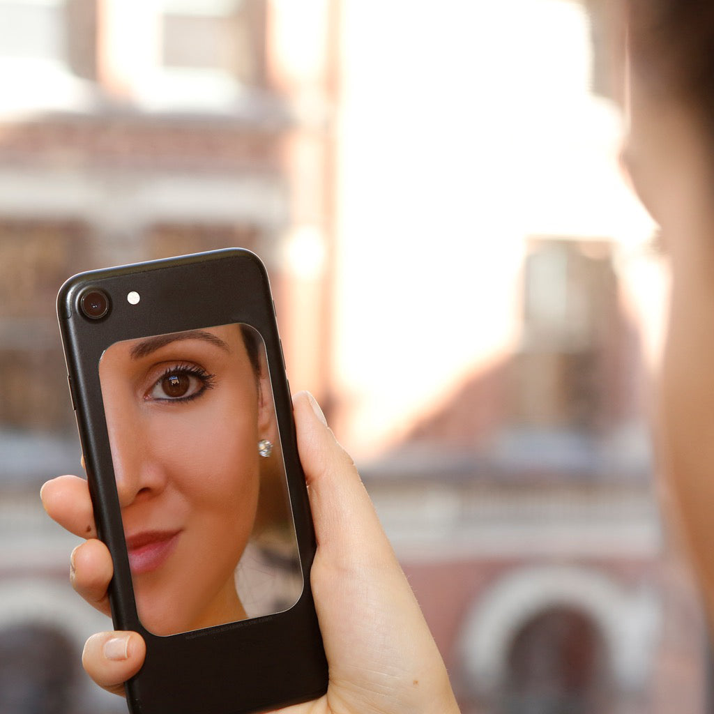 Woman looking in Phone Mirror.
