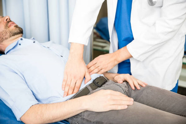 Doctor examining abdomen of patient Close up of hands of the doctor touching the abdomen of a patient in the emergency room stomach pain stock pictures, royalty-free photos & images