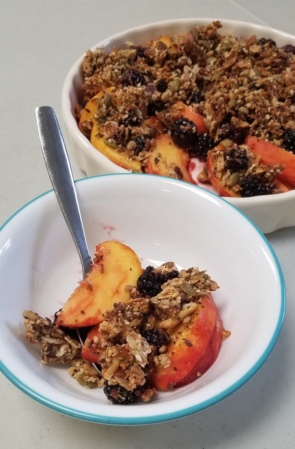 Peaches, blackberries and Singing Bowl No Grain Granola Crumble in a dish.