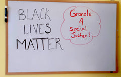 Office white board saying 'Black Lives Matter' and 'Granola 4 Social Justice'