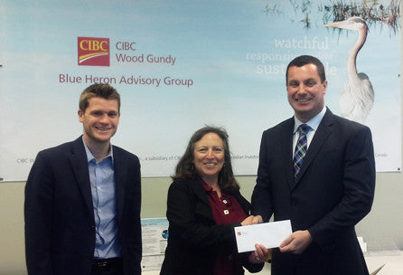 Neil Chappell of Blue Heron Advisory Group hands a cheque to Jessica Duncan of Singing Bowl Granola
