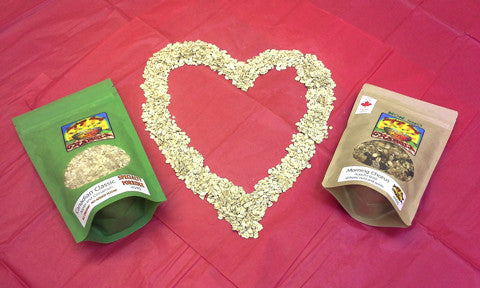 A heart made out of rolled oats on a red backcloth with a bag of Singing Bowl Granola either side