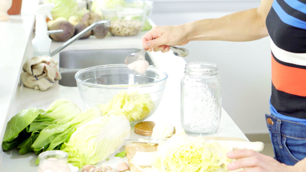 woman pouring salt onto vegetables in a bowl