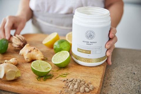 ketone energy container held next to a woman slicing lemons limes and ginger