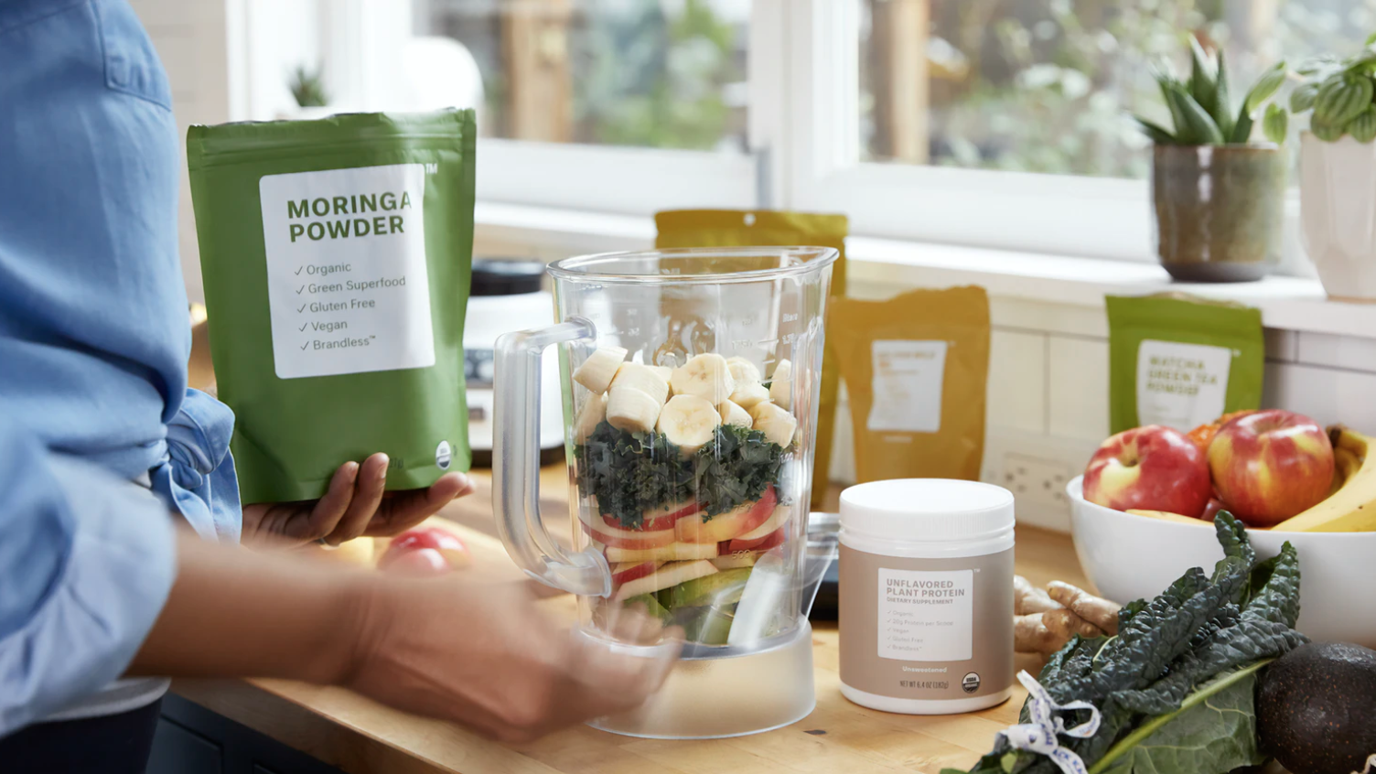 A woman puts greens powder keto supplements into a blender