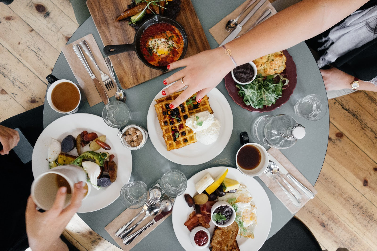 How to get rid of bloating: A table of people eating rich breakfast foods