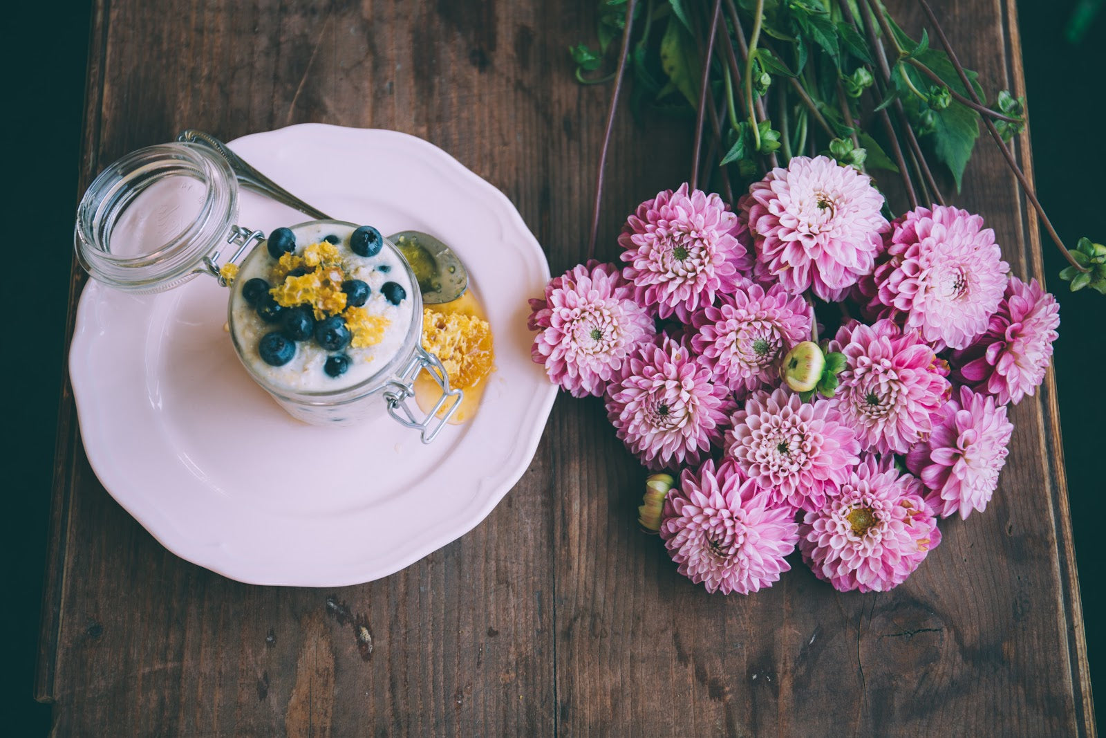 A mason jar of kefir yogurt surrounded by flowers