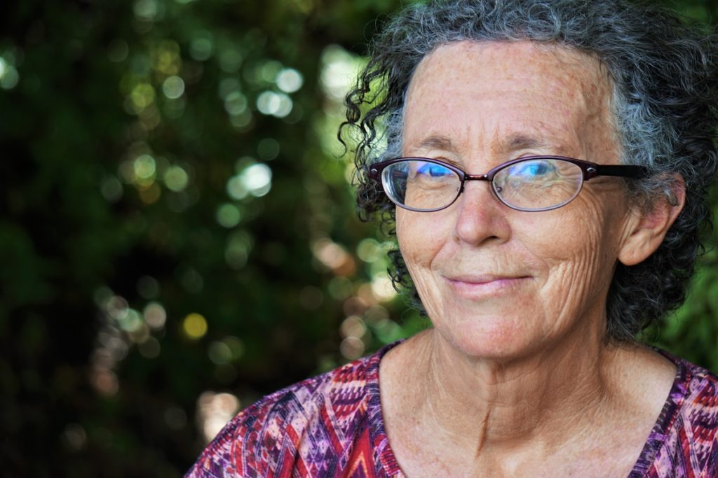 Menopause and anxiety: An older woman wearing glasses looks at the camera