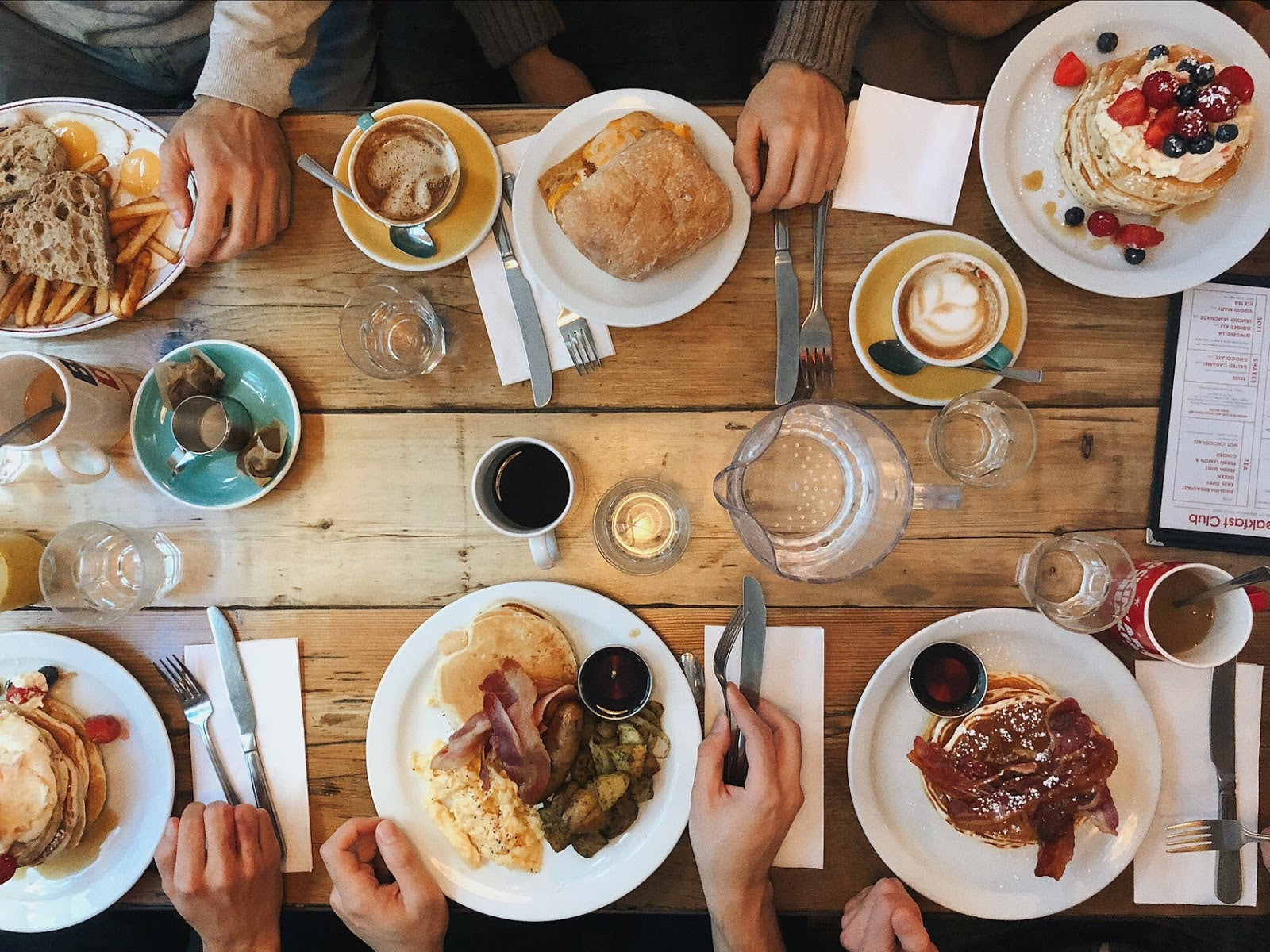 Best digestive enzymes: overhead view of people sitting at a table with plates of many different kinds of food