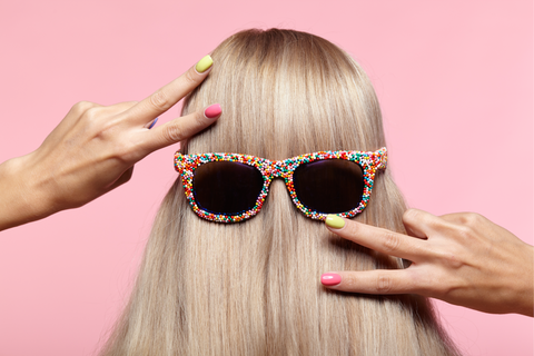 blonde with sunglasses on her hair gesturing a peace sign