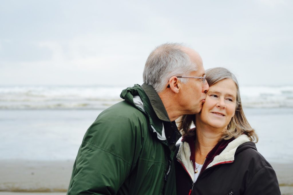 Menopause and anxiety: An older man kisses an older woman on the cheek as she looks away