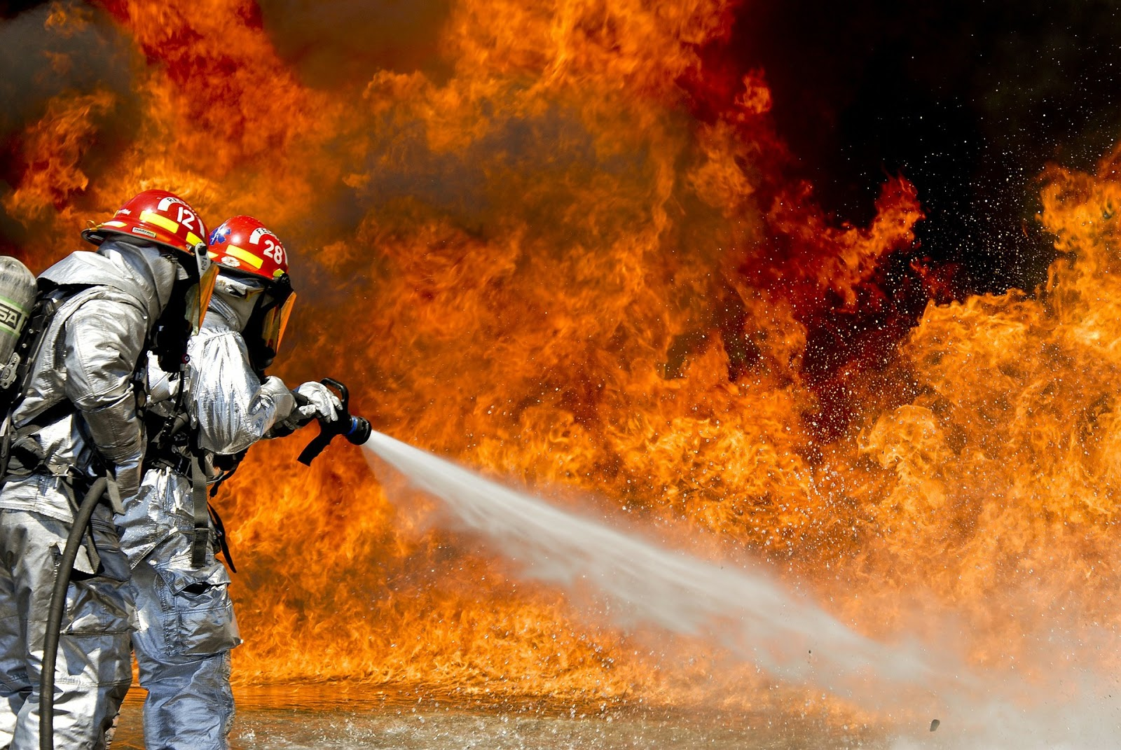 Herbs for inflammation: Fire fighters spray water on a large fire