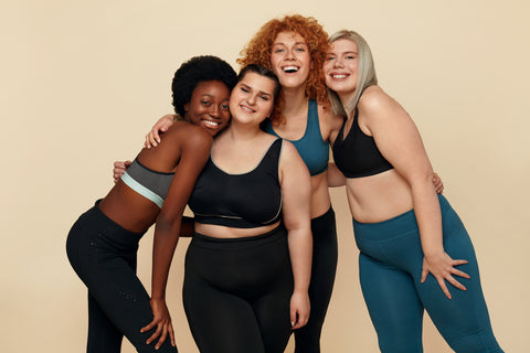 four women with different skin colors and body shapes standing together affectionately