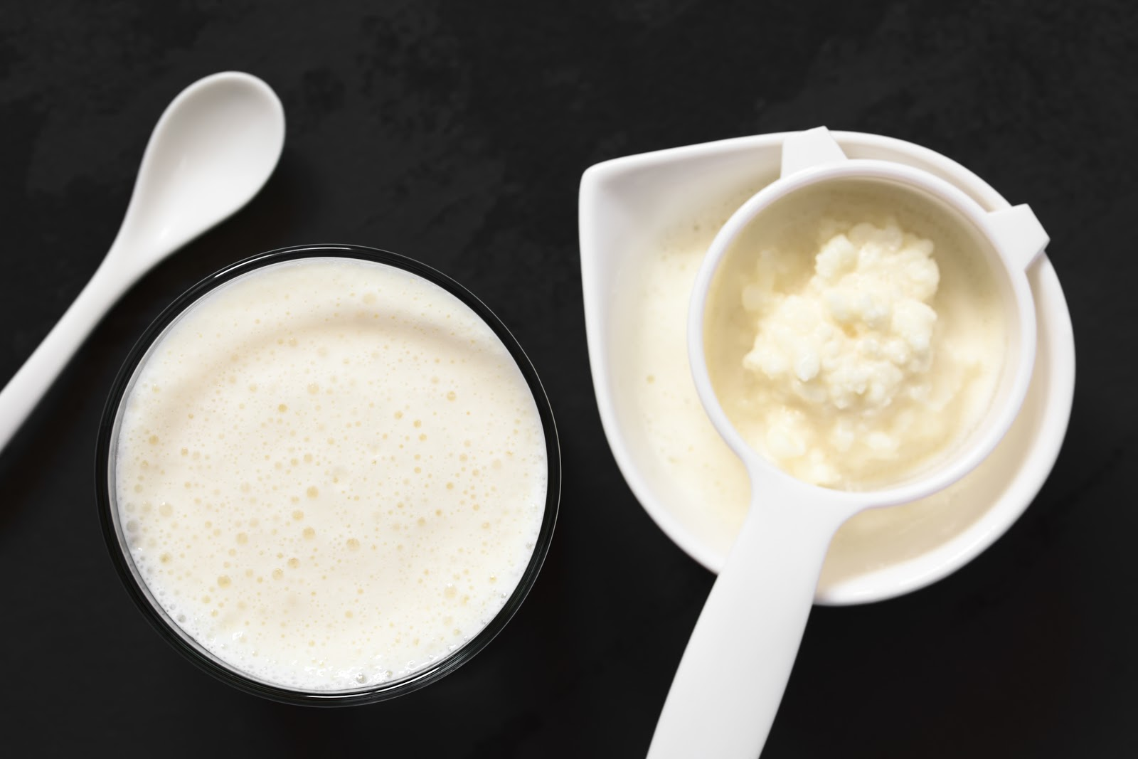 Benefits of kefir: Homemade kefir in a glass and sifting spoon