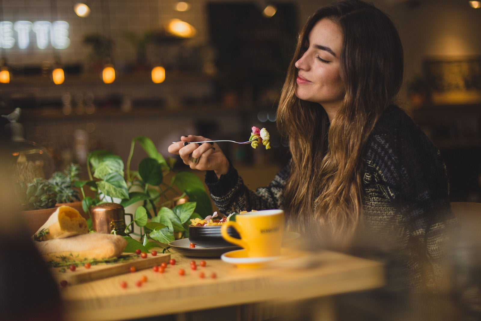 Gut rot: A smiling woman eating at a healthy restaurant