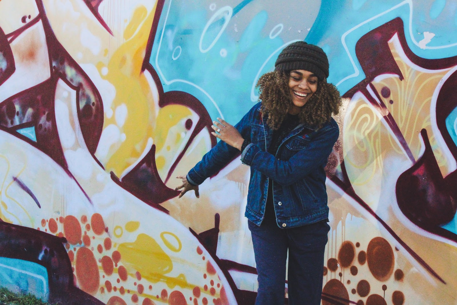 Gut rot: A happy woman in front of a colorful wall of graffiti