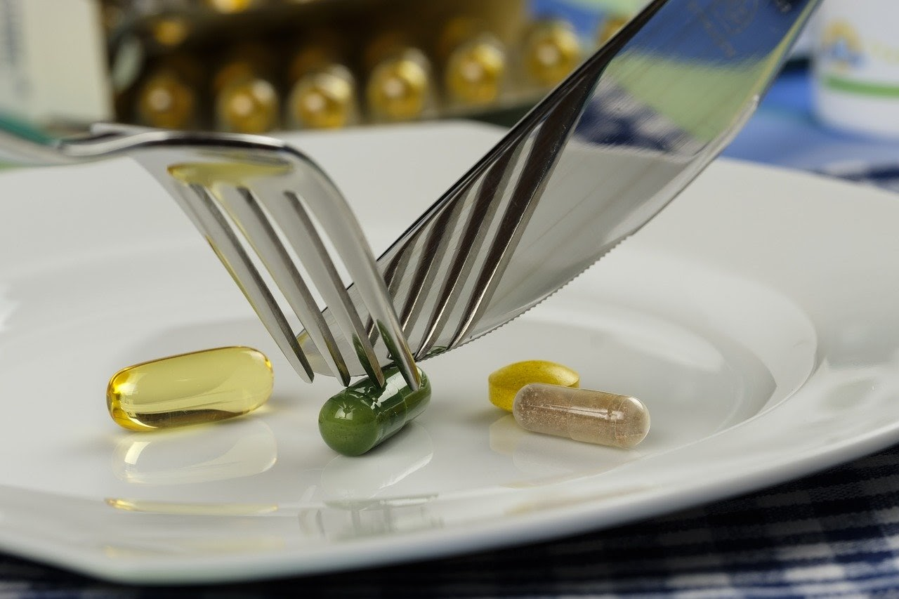 Best digestive enzymes: A fork and knife cutting a supplement pill