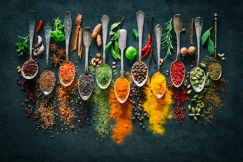 Spices on spoons on a black background