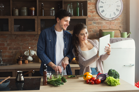Couple reading a recipe and cooking together
