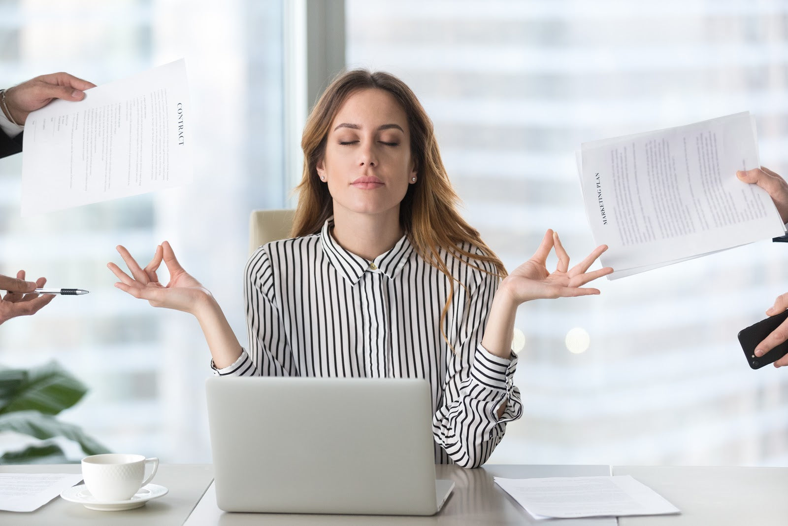 Woman meditating with eyes closed in front of laptop as people hold papers in front of her
