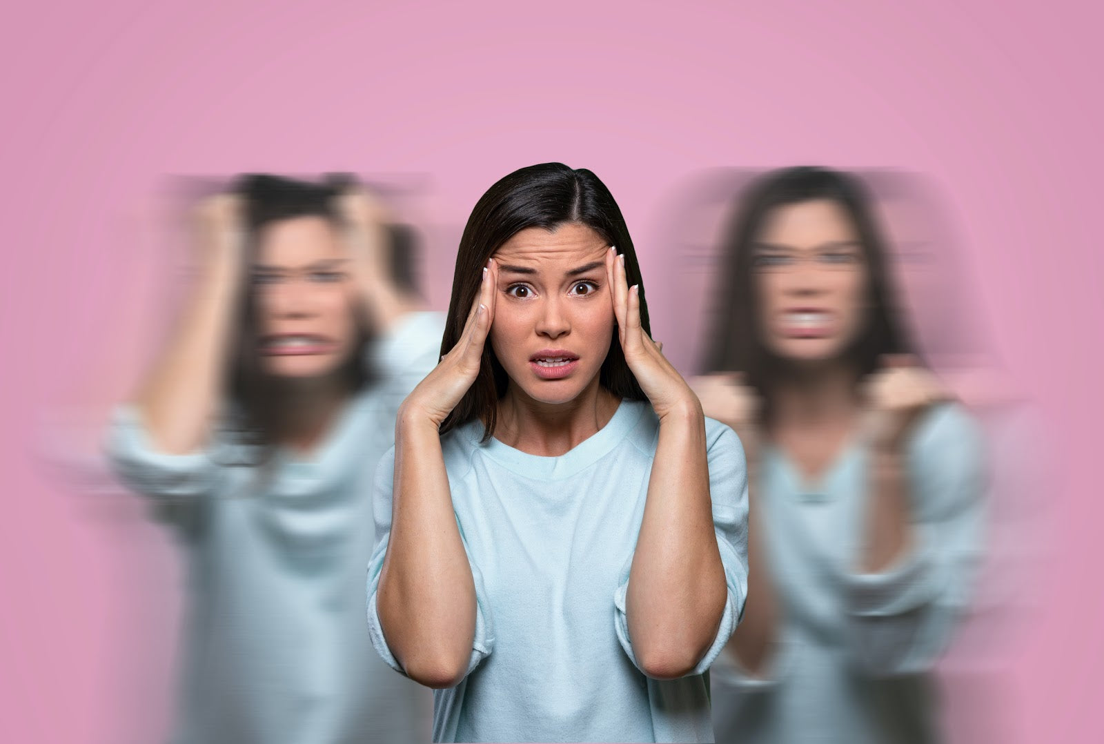Low Progesterone Symptoms: Woman who looks stressed with hands at her temples