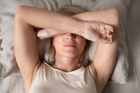 woman lying with her arms over her eyes