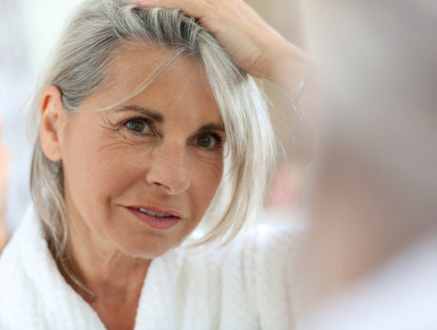 woman with grey hair looking in the mirror