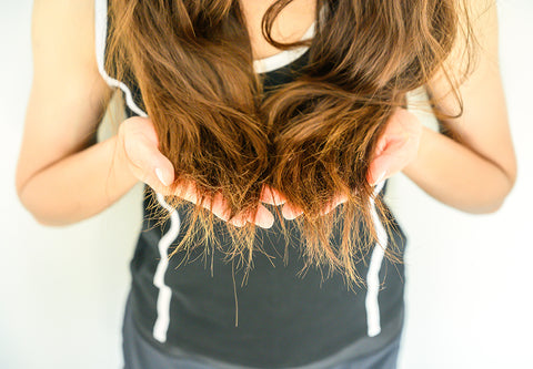 a woman with long brown hair cupping it in her hands