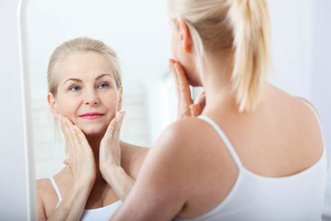 older woman looking in the mirror holding her face