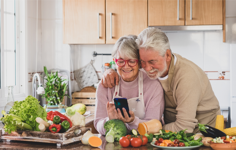 older couple hugging and smiling in the kitchen surrounded by vegetables