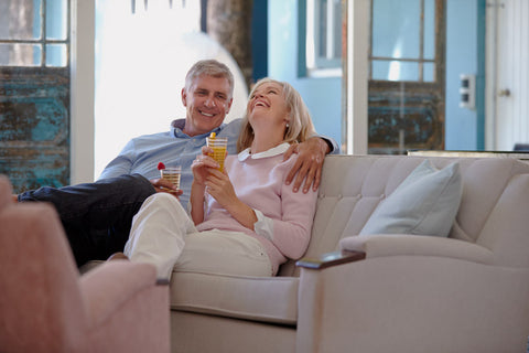 older couple laughing holding drinks