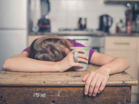 exhausted woman holding a coffee cup