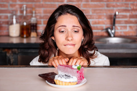 woman looking longingly at a piece of cake