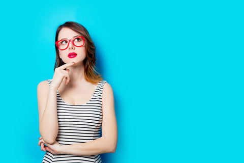 Woman thinking with red glasses on
