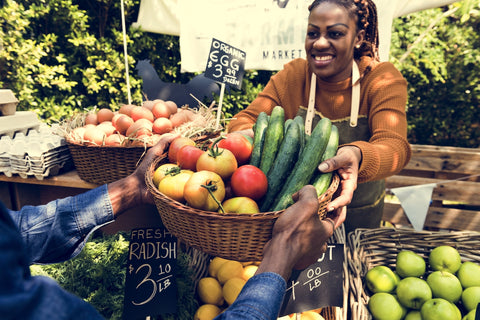woman at the farmers market handing a customer a basket of food