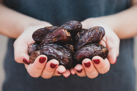 woman holding dates in her hands with red nails