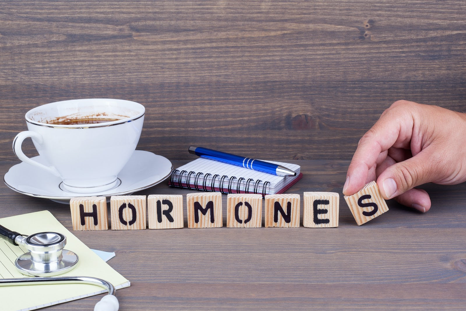 "Low Progesterone Symptoms: Wood tiles spelling out the word ""hormones"""
