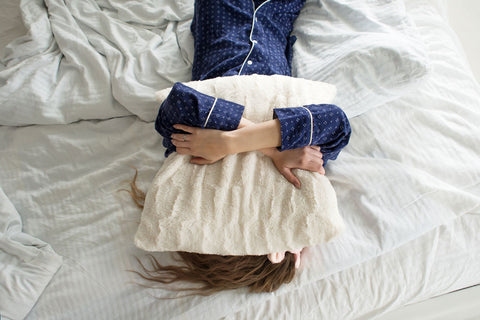 woman holding a pillow over her head laying on bed