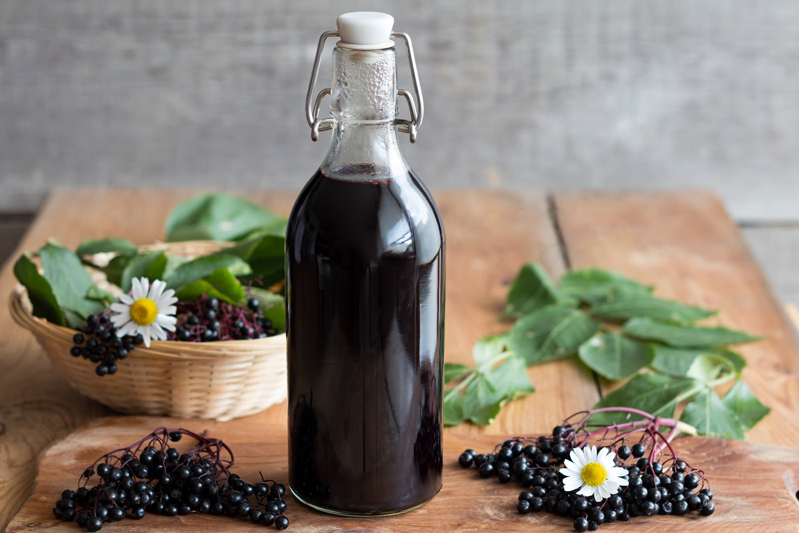 A bottle of elderberry juice next to piles of elderberries and antiviral herbs