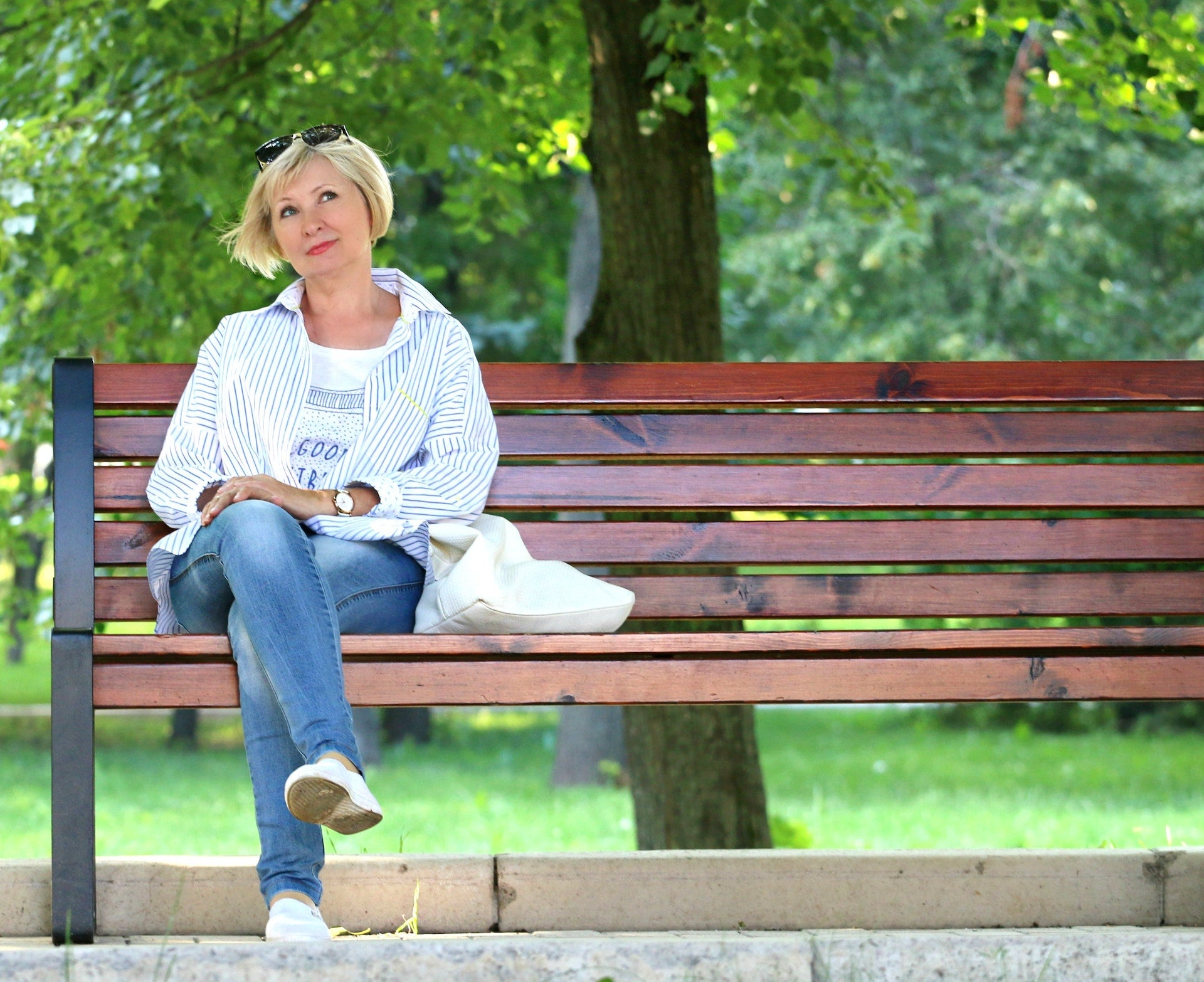Perimenopause supplements: A middle-aged woman sits on a bench