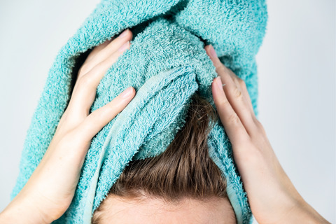 woman using blue towel on her hair