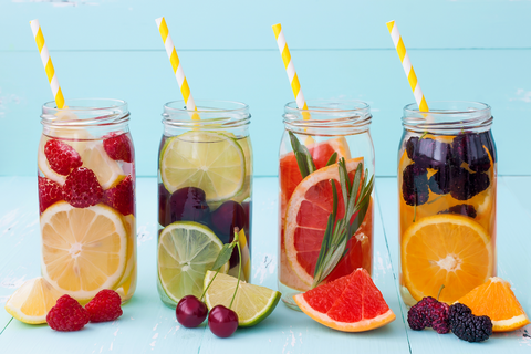 mason jars with striped straws filled with water and fruit