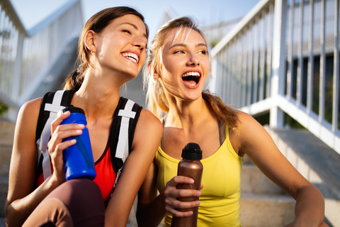 two athletic girls sitting with water bottles in their hands