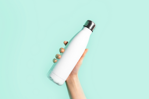hand holding a white water bottle