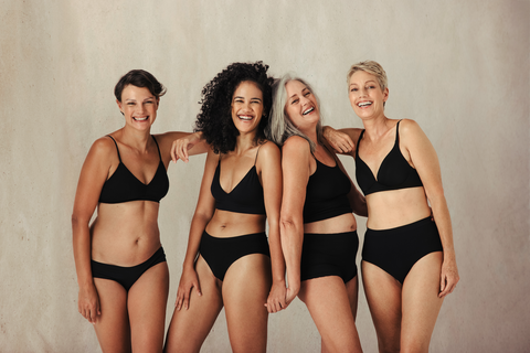 Four women in black underwear laughing together