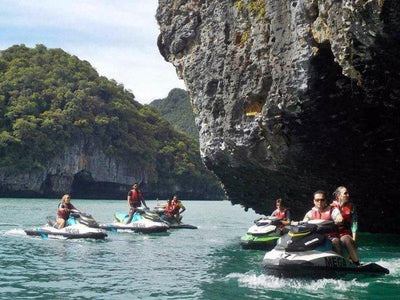 A group of tourists jetski near a cliff rock at Langkawi Islands